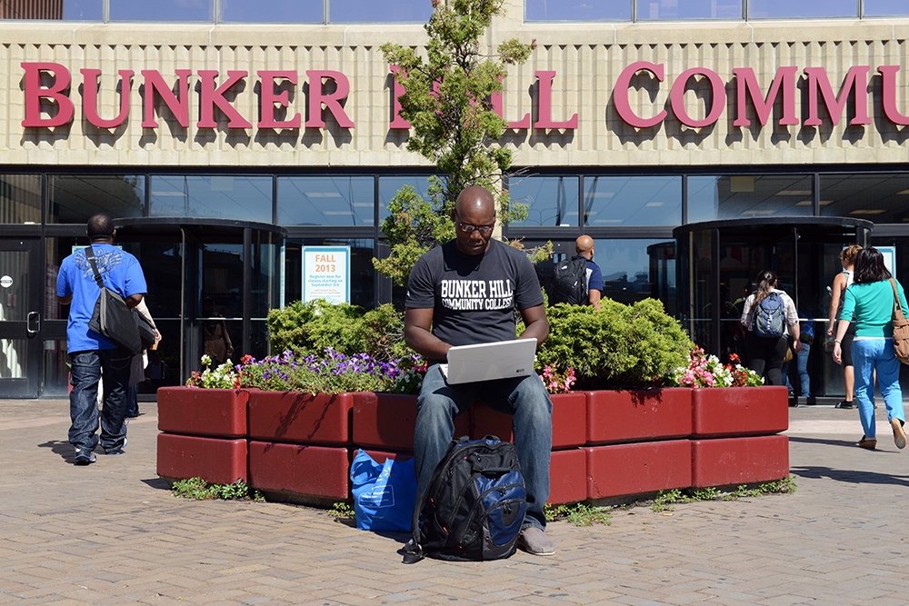 Osa Ohiomoba works on his laptop outside Bunker Hill Community College in Charlestown
