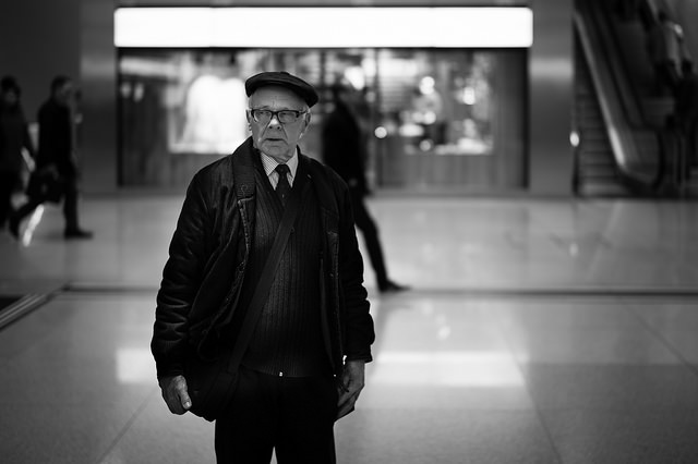 old man standing in a mall