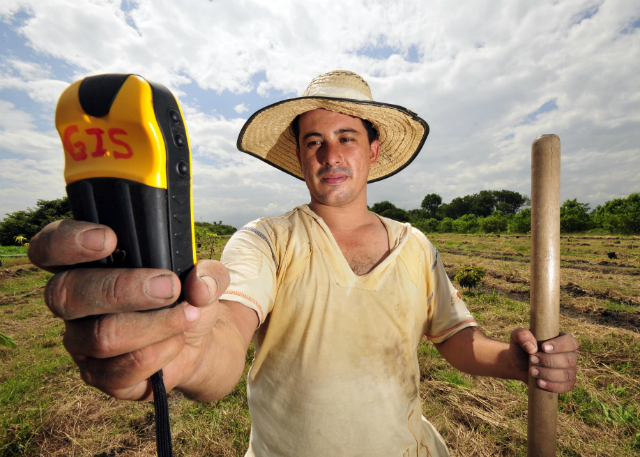 A farmer uses a handheld GPS device.
