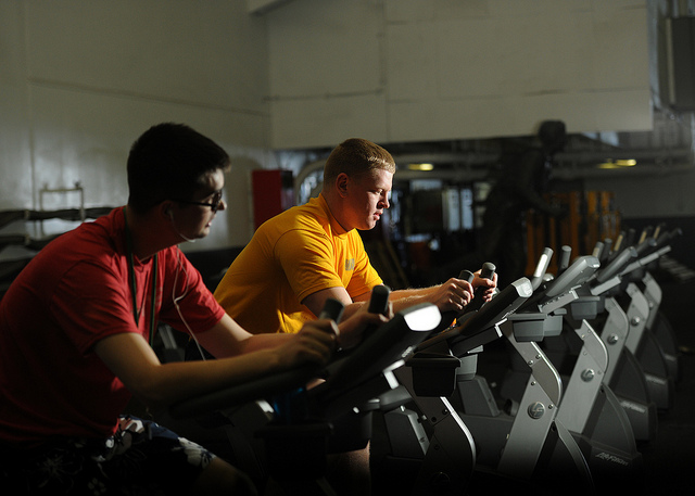 Two people exercise on stationary bikes. Credit: Official U.S. Navy Page / Flickr Creative Commons