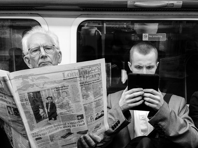 Older man reads a newspaper, a young man reads a tablet.
