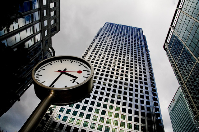 A clock beneath a skyscraper.